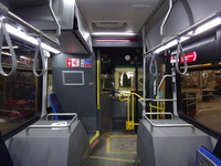 The interior of bus #7900 at CTA's South Shops Maintenance Facility on February  6, 2014. At the front of the bus, the most notable change from past CTA bus models is the more substantial protective barrier for bus operators. Elsewhere, the twin front seats behind the driver on CTA's previous generation Nova LFS buses have been replaced with a single, aisle-facing seat. Various computer equipment is located in a compartment suspended above this seat, necessitating a sign warning of the limited 175cm vertical clearance. Note the visible wiring for CTA's Ventra card reader, which was not yet installed at the time of this photograph.