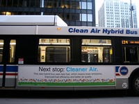 "Bus #809 at South Water and Michigan, working route #124 Navy Pier, on March 10, 2007. The lettering ""Clean Air Hybrid Bus"" and an accompanying advertisement inform the public that this is a special bus."